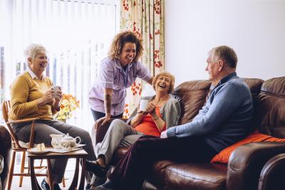 Three seniors enjoying tea and cake in the care home